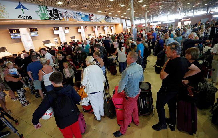 Op de luchthaven van Reus in Spanje staan tientallen Thomas Cook-klanten aan te schuiven voor meer nieuws.