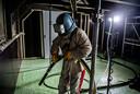 Een bouwvakker maakt zich klaar om verf met chroom-6 te verwijderen in een cabine die luchtdicht aan de onderkant van de Waalbrug hangt.