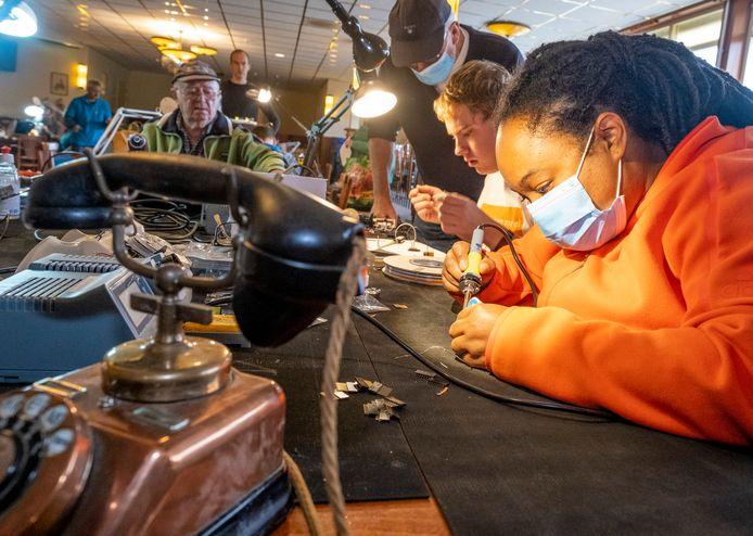 Er waren geen aanmeldingen voor burendag, maar de vrijwilligers van het Repair Café werkten wel gewoon door. Nihalia Blanken maakt een wonderfoon voor dementerende mensen. In de achtergrond (vlnr) Laszo Horvath, Jos van den Buijsch en Wilbert Huige.