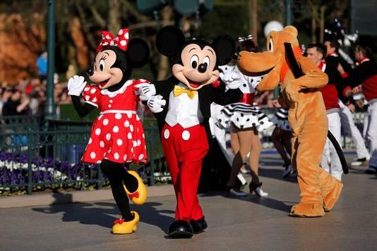 Micky en Minnie Mouse vermaken bezoekers in Disneyland Parijs, rechts Pluto.