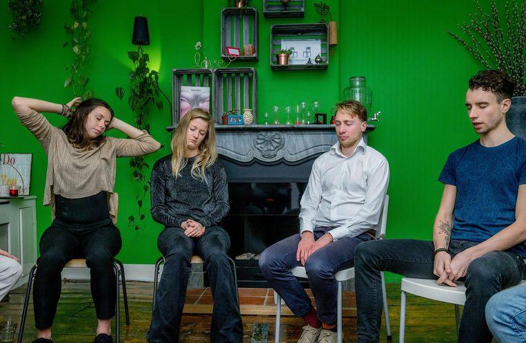 Deelnemers van The Therapy Club tijdens een meditatie. Rechts oprichter Rob van Drunen. Beeld Foto: Jean-Pierre Jans