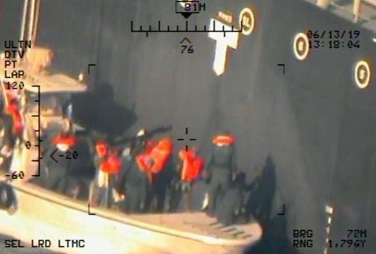 De beelden, die maandag werden vrijgegeven door het Pentagon, zouden gemaakt zijn vanuit een helikopter van de Amerikaanse luchtmacht. De mannen op de foto zijn volgens het Pentagon leden van de Iraanse Revolutionaire Garde die een onontplofte mijn verwijderen van het schip.  Beeld REUTERS
