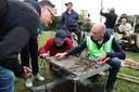 Wil Peels onderzoekt tijdens de Nationale Archeologiedagen in Valkenswaard op een zeef met behulp van omstanders de net geboorde grond. In de zeef zitten stukjes van een vaas