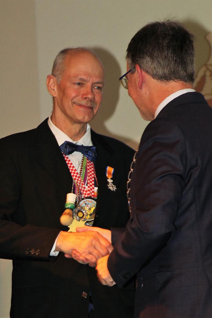 Frans van Luffelen ontvangt de versierselen die horen bij zijn onderscheiding.