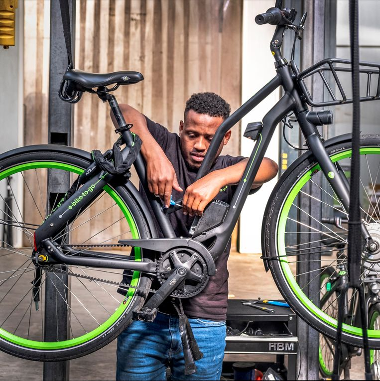 Een medewerker van E-bike to go repareert een van de fietsen. Beeld Raymond Rutting / de Volkskrant