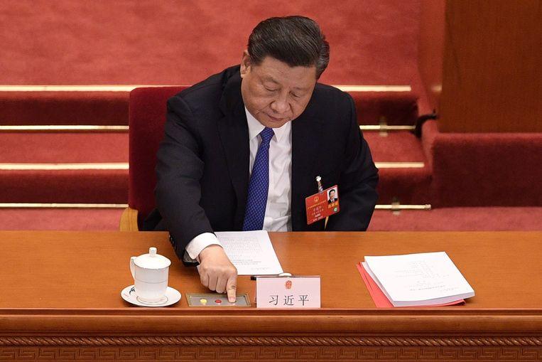 Een mogelijk nu al iconisch beeld: de Chinese president Xi Jinping drukt op het groene stemknopje bij de stemming in het Volkscongres. over de controversiële wet die de autonomie van Hongkong inperkt.