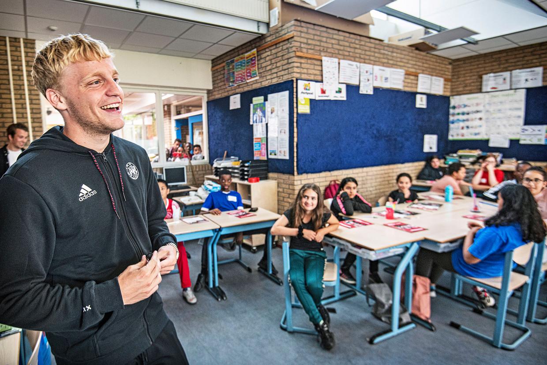Donny van de Beek moet lachen om een vraag van een leerling van de school Wereldwijs in Amsterdam-Zuid-Oost over waar hij volgend jaar voetbalt. Beeld Guus Dubbelman / de Volkskrant