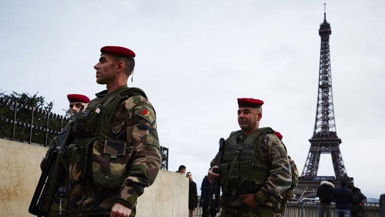 Militairen patrouilleren bij de Eiffeltoren in Parijs. Beeld anp