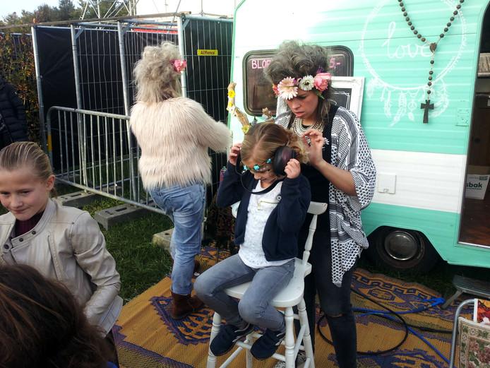 Kinderen kregen bij de kapster op Woudpop 2015 een 'chaoskapsel'.