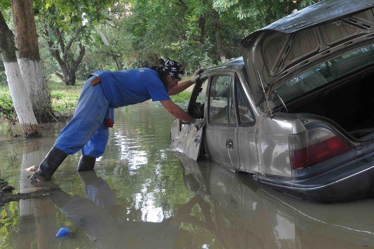 Een reddingswerker onderzoekt een gezonken auto na overstromingen in de Russische stad Kranodar in juli 2012. Bij hevige overstromingen kwamen toen zeker 171 mensen om het leven, tienduizenden mensen verloren al hun bezittingen.