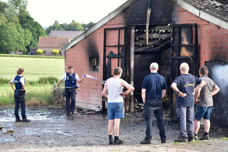 De kippenkweker en zijn vennoten kijken machteloos naar de uitgebrande stal, terwijl een agent een politielint ophangt.