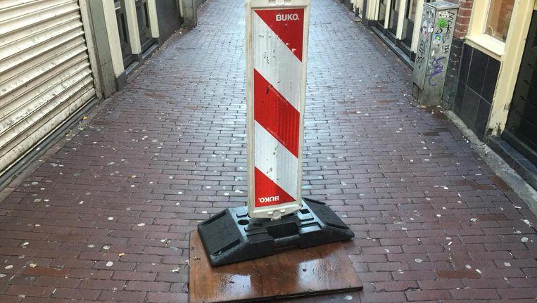 Er ligt inmiddels een houten plaat over het gat met een waarschuwingspaal. Beeld Eric Ankersmit