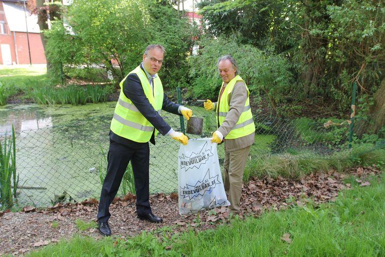 Schepenen Jan Desmeth (N-VA) en Luc Van Ruysevelt (CD&V) uit Sint-Pieters-Leeuw ruimen het park mee op aan de Witteweg.