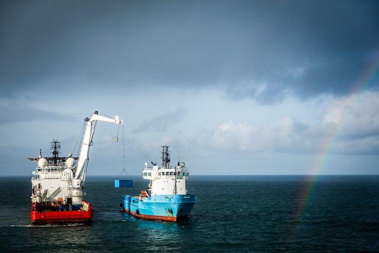 Een bergingsschip takelt een lege container van het schip Blue Bella om overboord geslagen puin van de MSC Zoe te bergen. Beeld null