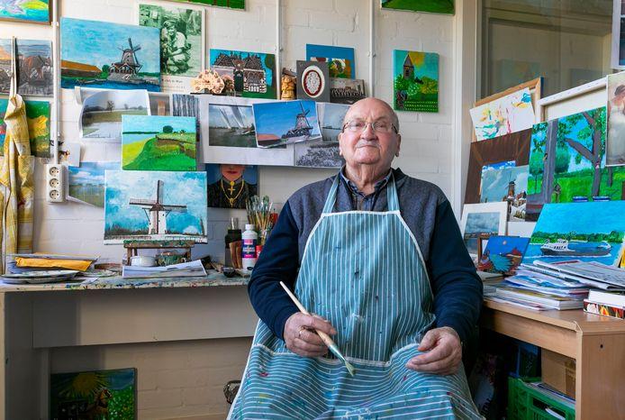 Ad de Hart in zijn atelier tussen de schilderijen van de omgeving Heusden en Herpt.