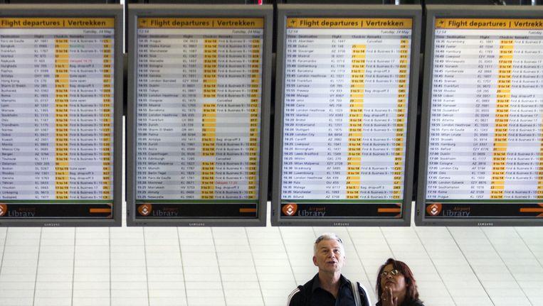 Reizigers bekijken de aankomst- en vertrektijden op Schiphol Beeld ANP