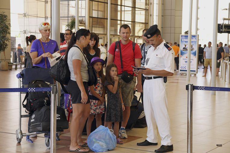 Britse toeristen wachten op een paspoortcontrole voordat ze terug naar huis vliegen. Beeld ap