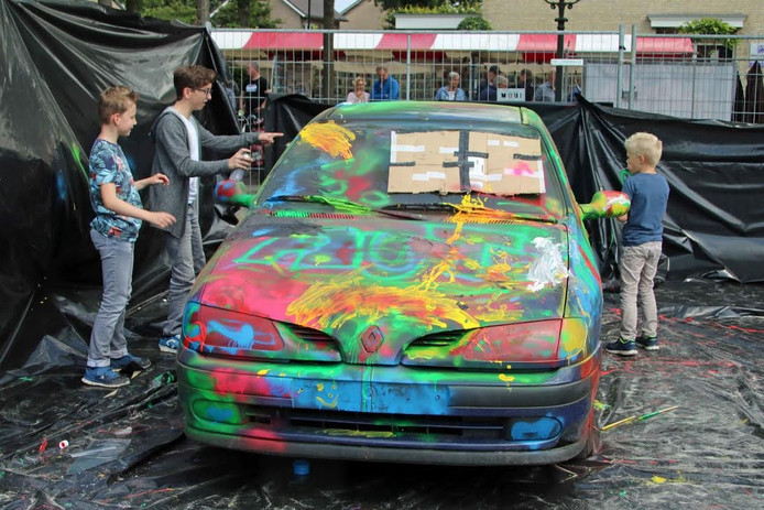 Kinderen genieten van het spuiten of verven een auto.