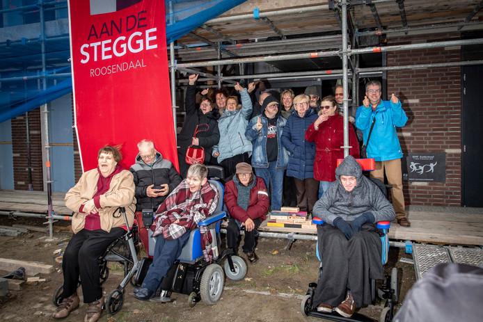 Toekomstige bewoners bij de eerste steen (rechts aan de gevel) van de nieuwe SDW- woonlocatie Zuiderdreef in Bergen op Zoom. Midden tussen de bewoners op de steiger, de door bewoners zelf gemaakte en versierde houten stenen, die later zullen worden onthuld bij oplevering.