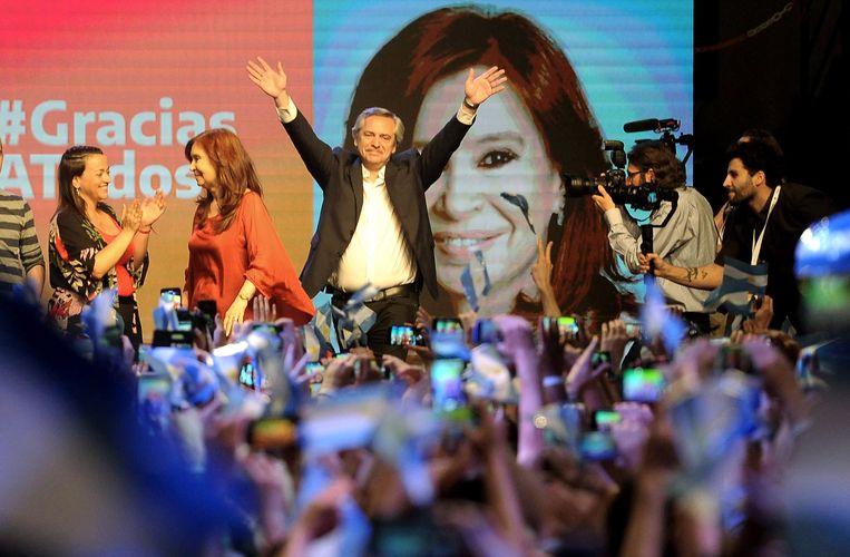 De nieuwe president Alberto Fernandez steekt de handen in de lucht. Op de achtergrond de afbeelding van Christina Fernandez de Kirchner.  Beeld EPA