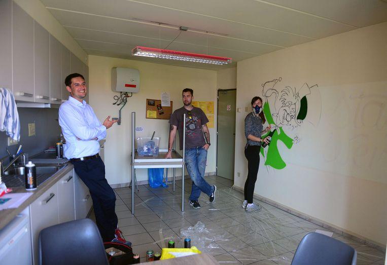 Kunstenares Jasmien aan het werk in de keuken van een kot, links Laurent Van Assche en rechts Matthew Dawn, die het project leidt.