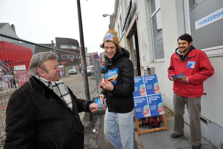 Leden van PVDA delen parkeerkaarten uit op de Grote Markt.