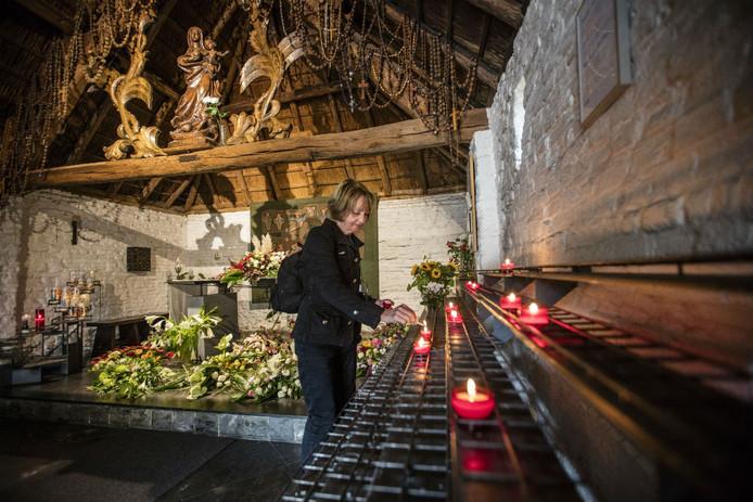 Annie van Gool steekt haar dagelijkse kaarsje aan in de kapel.