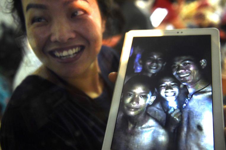 Een opgeluchte familielid van een van de kinderen houdt een foto vast met vier van de in de grot opgesloten jongens.