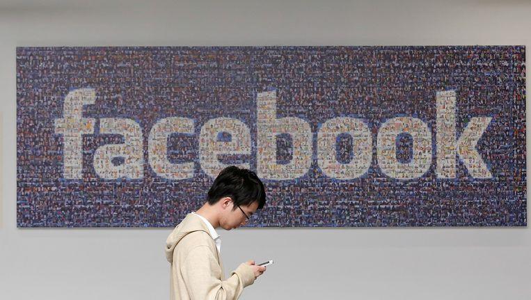 Een Facebook-logo aan de muur in een gebouw op de Facebook-campus in Menlo Park, Californië. Beeld ap