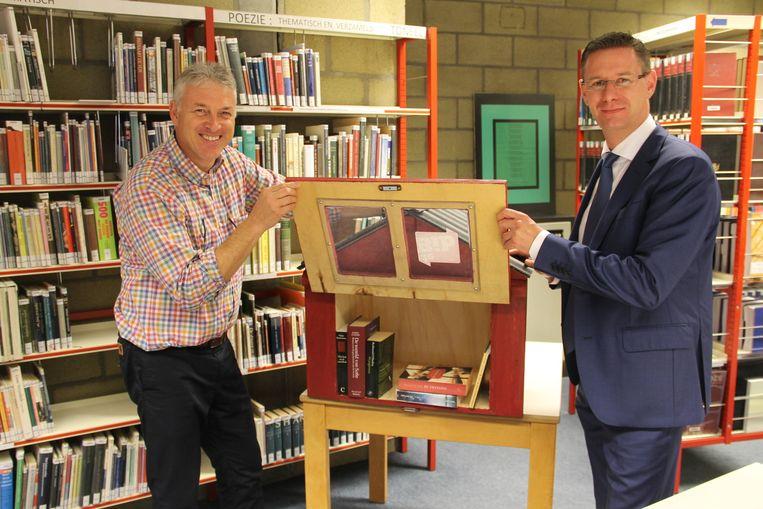 Bibliothecaris Nicolas Cappelle en bibschepen Kurt Himpe (N-VA) vullen het eerste boekenruilkastje.