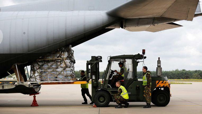 Een transportvliegtuig van de Koninklijke Luchtmacht wordt op vliegbasis Eindhoven geladen met hulpgoederen voor Noord-Irak. Beeld ANP