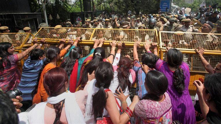 Betogers proberen een metalen barricade omver te werpen. Beeld ap