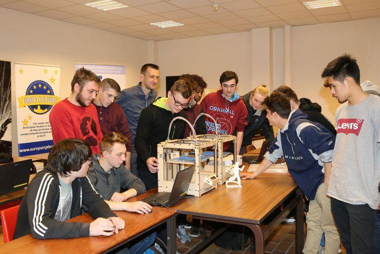 Enkele leerlingen volgen geboeid de workshop '3D-printen en modelleren'.