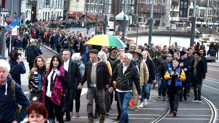 Demonstranten in Amsterdam lopen hand in hand tijdens een protestmars tegen homogeweld op woensdag 5 april. Beeld null