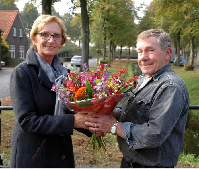 Lia van Delft geeft Kees Godee een bos bloemen.