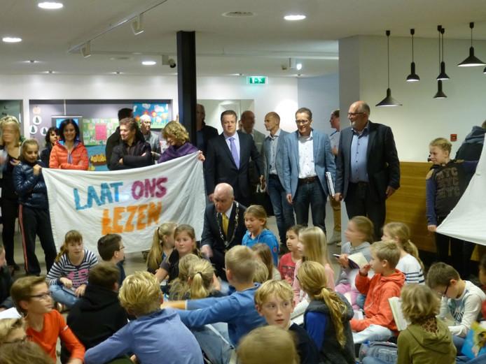 Burgemeester Prick praat met leerlingen van groep 7&8 van basisschool De Schakel die protesteren tegen de voorgenomen bezuinigingen op de bibliotheken in Maasdriel. Achter hem een deel van de CDA-fractie in Maasdriel.