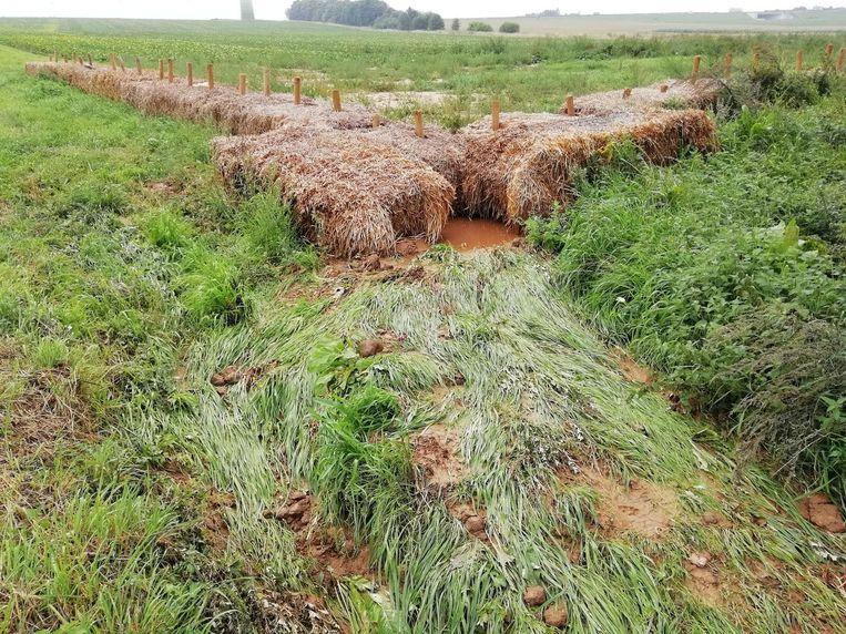 De modder stroomde door het gat in de dam naar het dorpscentrum.