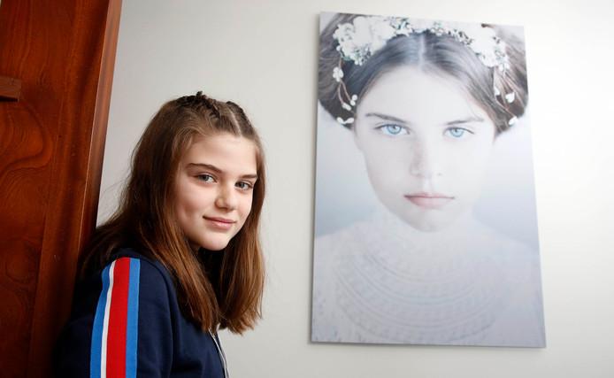 Esmée van den Broecke uit Hulst poseert bij de grote foto in de hal die sinds kort op de cover van een Italiaanse roman prijkt.