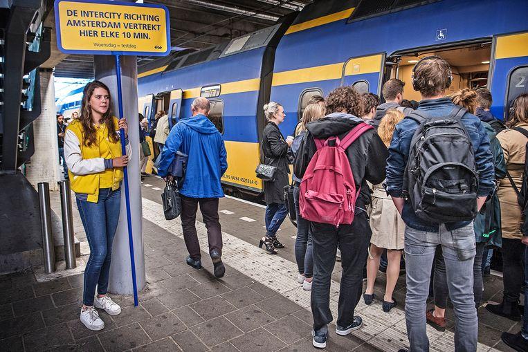 Een NS-medewerkster maar reizigers op Utrecht CS bekend met de nieuwe dienstregeling.  Beeld Guus Dubbelman / de Volkskrant