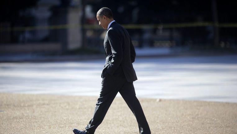 Obama loopt over straat naar het Witte Huis. Beeld epa