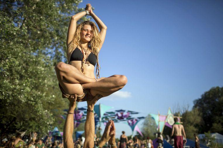 Een vrouw wordt omhoog gehouden door de voeten van een man en doet een yogapose tijdens het Samsara Yoga and Music Festival in Siofok, Hongarije. Beeld EPA