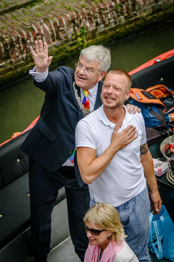 Van Zanen tijdens de Canal Parade in 2018. Samen met organistor Robbert Kalff zwaait hij naar mensen op de kade.