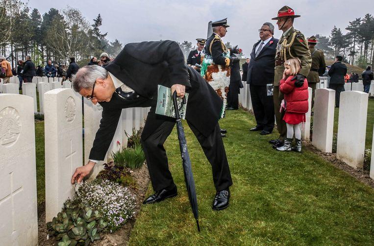 Een bezoeker legt een kruisje neer aan één van de grafstenen.