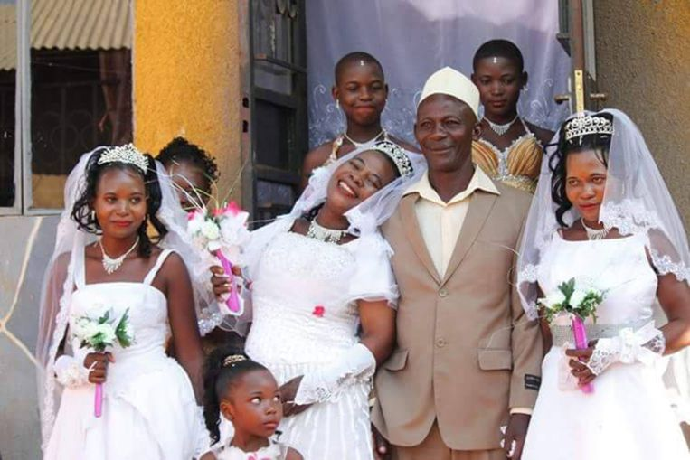 Mohammed Ssemanda geflankeerd door zijn drie bruiden.