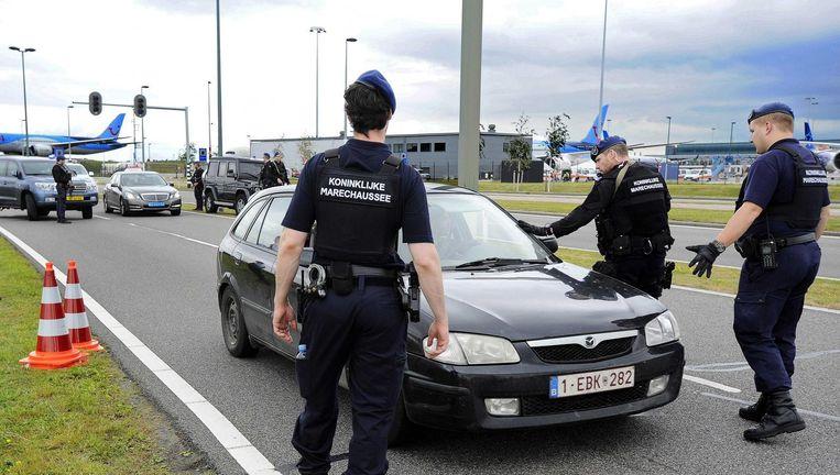 Leden van de Marechaussee voeren controles uit bij voertuigen rond de luchthaven. Beeld ANP