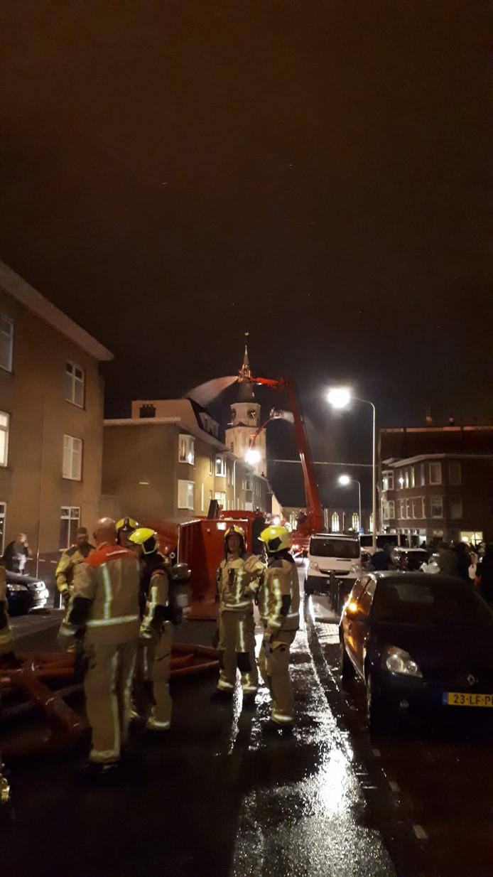 Hoogwerkers houden woningen rond de Scheveningse kerk nat.