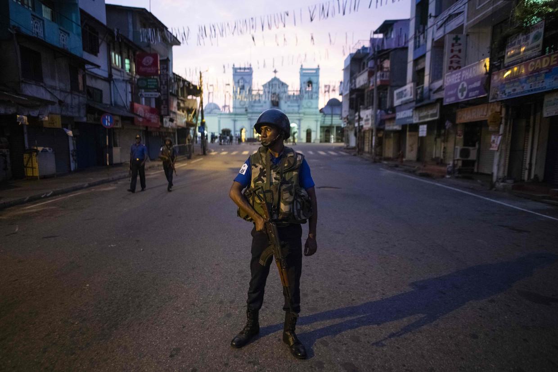 Een militair staat voor de roomskatholieke Sint-Antoniuskerk in Colombo, waar zondag een van de aanslagen plaatsvond. Beeld AFP