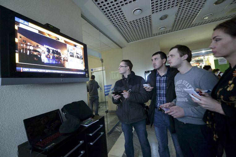 Journalisten kijken naar het nieuws over het gecrashte toestel van Flydubai. Beeld reuters