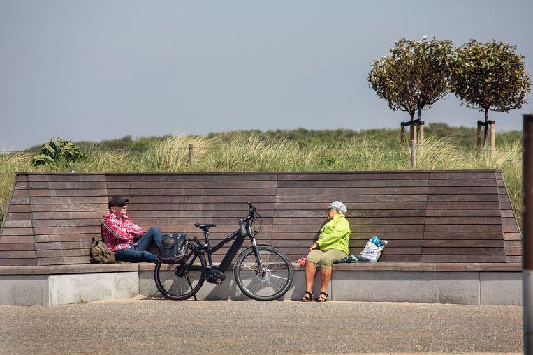 Twee ouderen op gepaste afstand op een bankje.  Beeld Arie Kievit