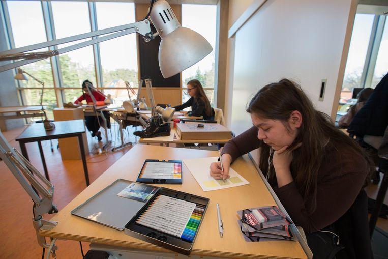 Een leerlinge werkt ideeën uit aan de tekentafel.
